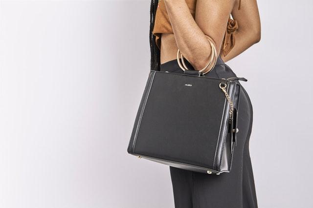 Žena držící na lokti elegantní kabelku